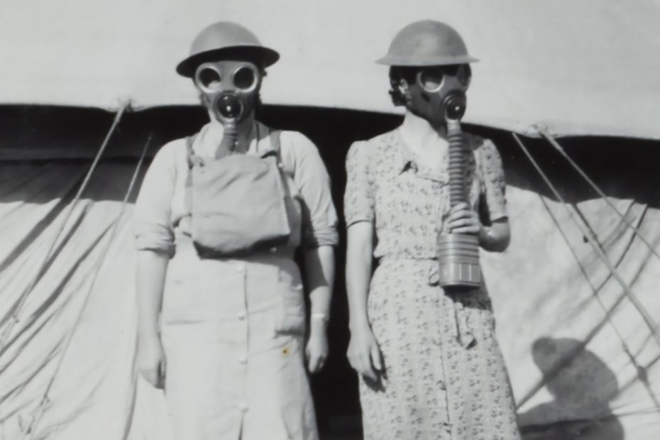 WWII-era photo of two women wearing gas masks.